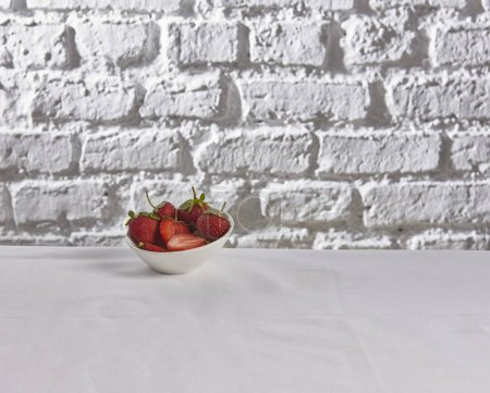 Photo for Strawberries behind brick wall white background - Royalty Free Image