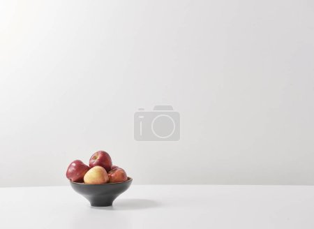 Photo for White table and red apples - Royalty Free Image