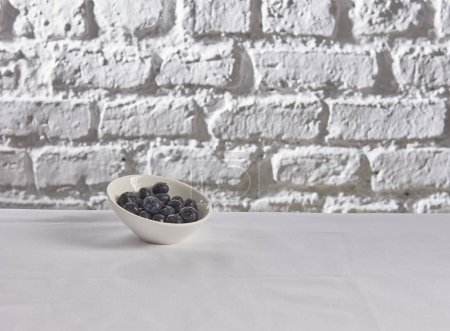 Photo for Blueberries behind brick wall white background - Royalty Free Image