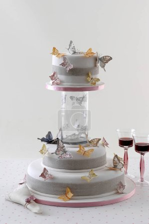 Photo for Wedding cake with red wine glasses behind white wall - Royalty Free Image