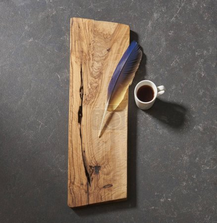 Photo for Black background cutting board with feather  and coffee - Royalty Free Image