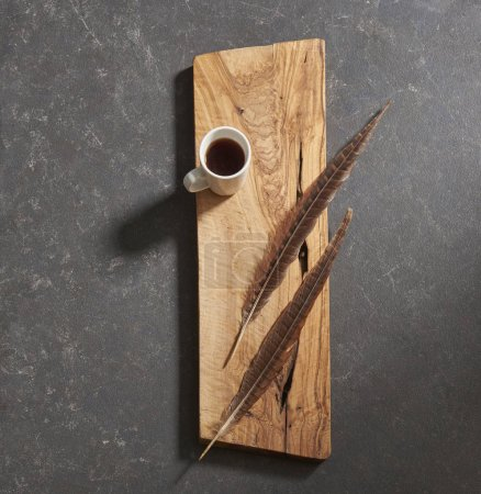 Photo for Black background cutting board with feathers  and coffee - Royalty Free Image