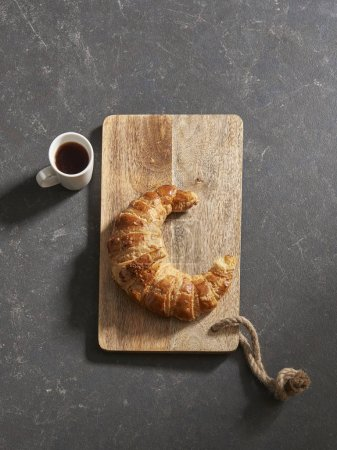 Photo for Black background ,coffee cup and cutting board with croissant - Royalty Free Image