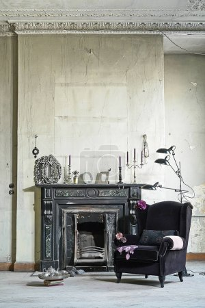 Photo for Old black fireplace with armchair, decorative former white wall. - Royalty Free Image