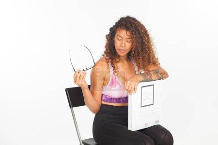 Atleta chica con un libro en la mano, en una fase de relajación sentado en una silla .