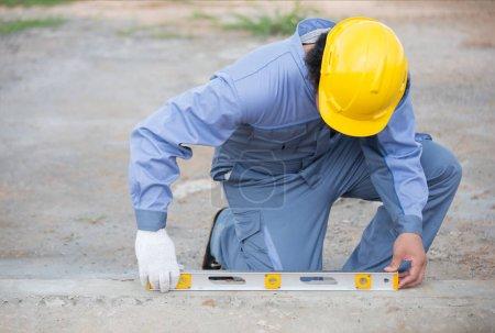 Photo pour Menuisier sur chantier à l'aide d'une règle d'eau ou d'une goulotte pour la mesure sur ciment - image libre de droit