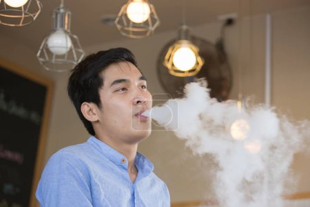 Photo pour Jeune homme asiatique portant un T-shirt bleu, expirer avec de la fumée de tabac ou de cigarette - image libre de droit