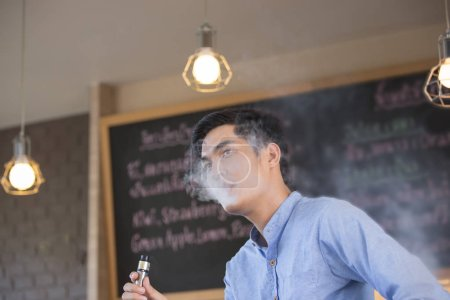Photo for Young Asian man wearing blue T-shirt, exhale with smoke from tobacco or cigarette - Royalty Free Image