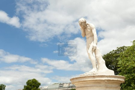 PARIS, FRANCE - 02 June 2018: A facepalm statue. In The Garden Of Tuileries, near Louvre. Cain after the murder of his brother Abel. Sculpture by Henri Vidal ,1896 .Jardins des Tuileries.