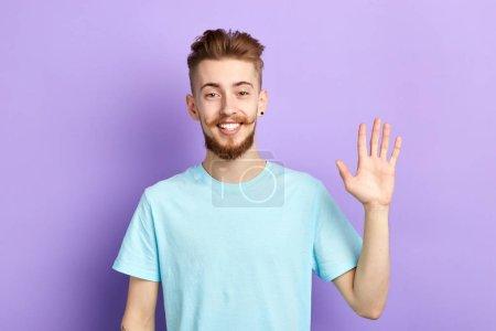 Photo pour Un homme joyeux et positif montrant ses émotions humaines, ses expressions faciales, un bel homme agitant la main, bonjour, bonsoir, à plus tard. fond bleu isolé, plan studio - image libre de droit