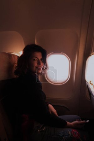 Young woman sitting on passenger seat near window inside airplane