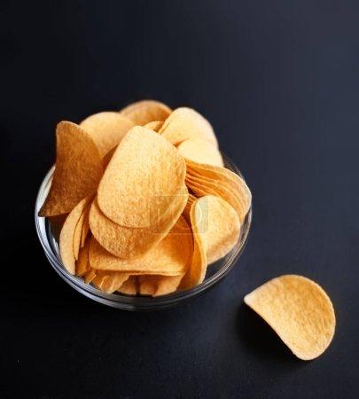 Potato chips on dark  background with copyspace. Top vie