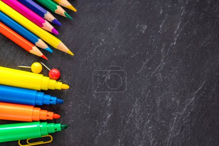 School supplies on black chalk  board background, top view. Back to school and Education concept.  Flat lay, copy-space