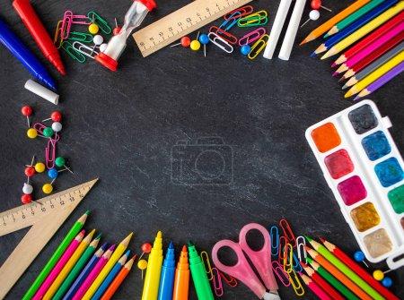 Back to school Background. School supplies on black chalk board. Flat lay