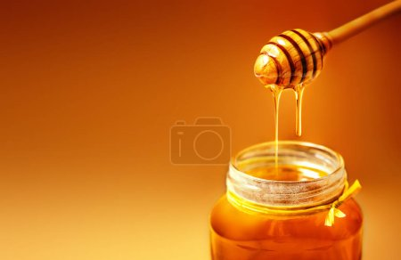 Photo for Honey in jar with honey dipper on rustic wooden table background. Copy space. - Royalty Free Image