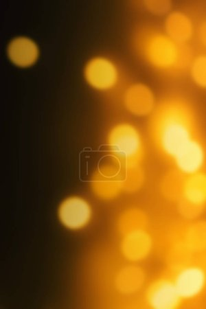 Golden  Christmas bokeh lights on dark Background.  Abstract Yellow  glowing defocused lights, copyspace