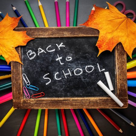 Photo for School supplies with Stationery and chalkboard with colorful pencils and autumn leaves on black board background. Back to school. Flat lay - Royalty Free Image
