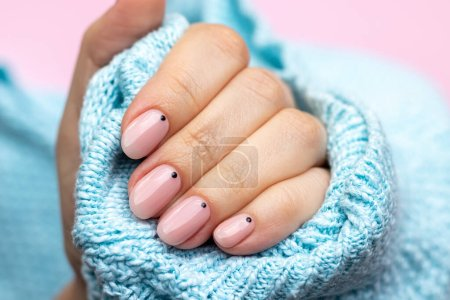 Photo pour Female hand in a blue knitted sweater fabric with trendy beautiful manicure - pink nude nails with black small dots on a pink background. Selective focus. Closeup view - image libre de droit