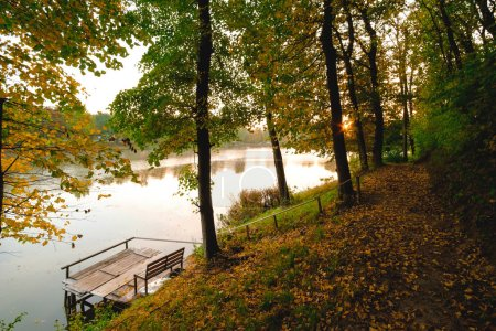 Photo for Autumn foliage lake in morning with pier - Royalty Free Image