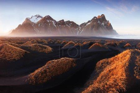 Photo pour Vue scénique des montagnes rocheuses et de l'herbe au coucher du soleil - image libre de droit