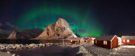 Photo pour Vue panoramique des aurores boréales vertes au-dessus des maisons - image libre de droit