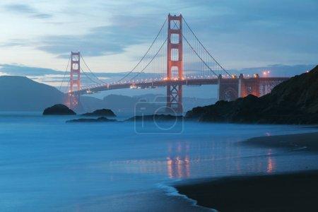 Photo pour Vue panoramique classique du célèbre Golden Gate Bridge vue de la pittoresque plage Baker Beach en belle lumière du soir dorée sur un coucher de soleil avec ciel bleu et nuages en été, San Francisco, Californie, États-Unis - image libre de droit