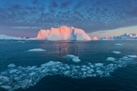 Photo for Stranded icebergs in the fog at the mouth of the Icefjord near Ilulissat. Nature and landscapes of Greenland. Travel on the vessel among ices. Phenomenon of global warming. Coast in the sunset. - Royalty Free Image