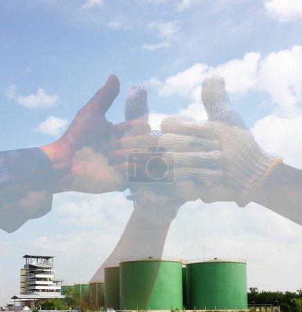 Photo pour Double exposition des pouces vers le haut avec le fond de paysage d'usine. l'équipe travaille les pouces vers le haut après le succès dans le projet que l'usine de transformation d'huile végétale. - image libre de droit