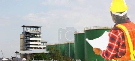 Photo pour L'ingénieur en costume de sécurité tenant plan en main et lloing au projet de traitement d'huile végétale.l'ingénieur de consultants vérifie la disponibilité avant de faire fonctionner des machines - image libre de droit