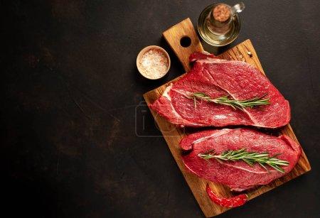 Photo pour Deux gros steaks crus de New York avec des ingrédients sur une planche à découper. sur le fond de pierre sombre. avec espace de copie - image libre de droit