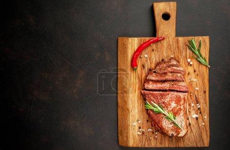Photo pour Steak New York angus noir prêt-à-manger avec ingrédients sur une planche à découper. Repas prêt pour le dîner sur un fond de pierre sombre. avec espace de copie - image libre de droit