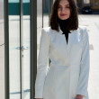 Elegant young woman dressed in a short white coat ...