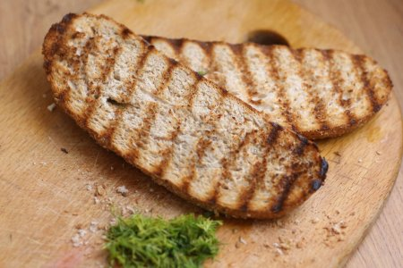 Two grilled bread toast slices with shreded dill o...