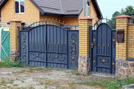 Photo for Black metal gates and doors with a forged pattern and part of a brick fence - Royalty Free Image