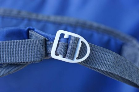 Foto de Un mosquetón blanco en un arnés gris sobre un fondo azul - Imagen libre de derechos