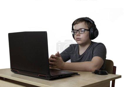 Photo pour Garçon avec un casque en regardant l'écran du portable et l'écoute d'apprendre. isoler - image libre de droit