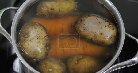 Photo for Hot boiling pan with vegetables potatoes and carrots. Cooking in a pan on the home kitchen - Royalty Free Image