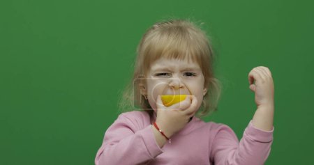 Photo for Beautiful young girl eats a lemon with a grimace on her face. Green screen. Chroma Key - Royalty Free Image