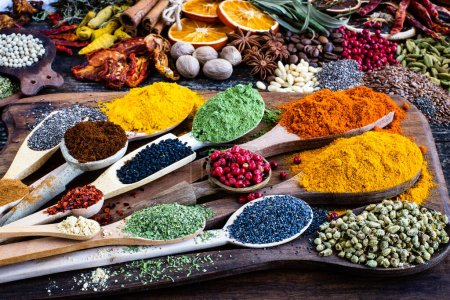 Photo for Many colorful spices, herbs and dried fruits on the wooden rustic table. Spices in the spoons and bowls with top view. - Royalty Free Image