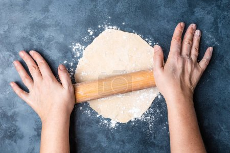 Photo for Top view of person hands rolling wheat dough on table - Royalty Free Image