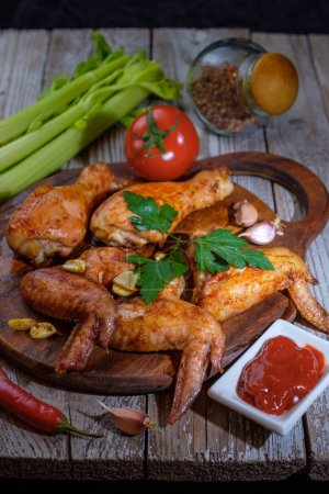 Photo for Roasted chicken wings on wooden board with sauce and vegetables - Royalty Free Image