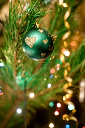 Foto de Green ball adorno de Navidad con patrón de corazones en abeto festivo - Imagen libre de derechos