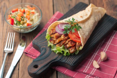Photo for Homemade shawarma with grilled meat and salad bowl on rustic table - Royalty Free Image