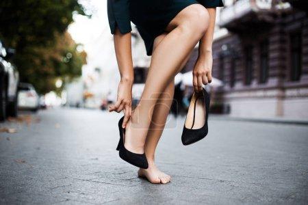 Photo pour Liberté classique chic robe-code matin lever du soleil après nuit club massage porter épuisé fille concept. Lire derrière vue arrière gros plan photo de fesses cul main décoller chaussures noires inconfortables - image libre de droit