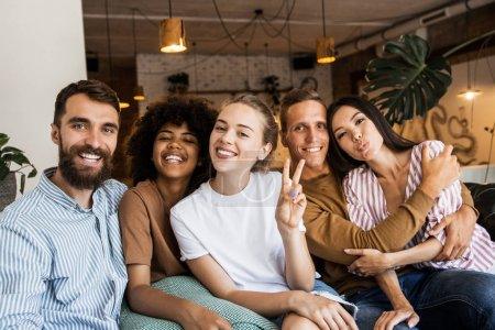 Happy multi ethnic young people looking at camera, smiling diverse friends or students showing peace sign, multicultural millennials posing together at meeting, tolerance and racial equality concept