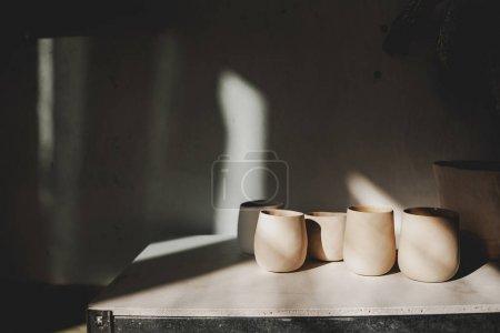 Photo pour Plats faits à la main en argile à partir de matériaux environnementaux. Tasse pour café ou thé. Film de cinéma. En atelier du maître de sculpture. ECO friendly. Mouvement tendance dans le plat - image libre de droit