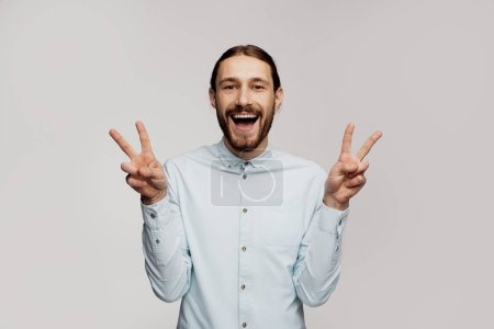 Photo for Free crazy young male hippie with pleasant smile, ready for party during all night after office work, expresses positive emotions, poses against grey background. Pleased hippy hipster guy. - Royalty Free Image