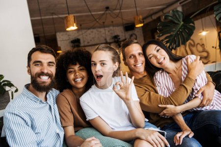 Photo for Happy multi ethnic young people looking at camera, smiling diverse friends or students showing peace sign, multicultural millennials posing together at meeting, tolerance and racial equality concept - Royalty Free Image