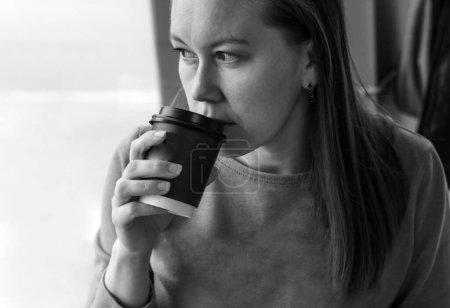 Foto de Retrato de una mujer de mediana edad tomando café en la cafetería de cerca. Parece pensativamente por la ventana - Imagen libre de derechos