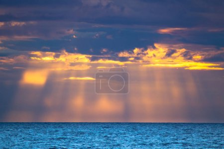 Photo for Sun rays from the clouds. Sun rays on the water. Evening at the sea. Calm. - Royalty Free Image